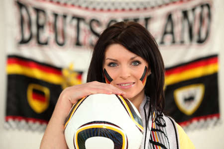 supporter: Female German soccer supporter stood holding ball