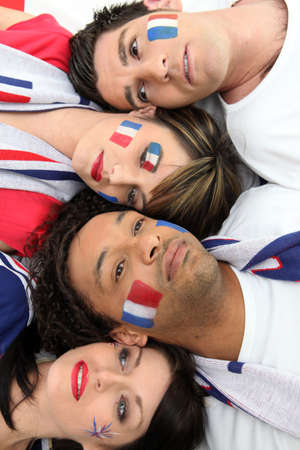 looker: Four French sports fans laying together Stock Photo