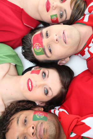 Four Portuguese soccer fans laying down together photo