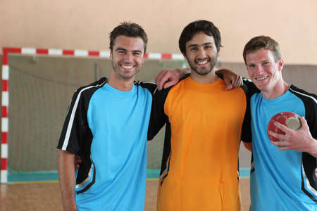 indoor soccer: Three grinning footballers in front of goal Stock Photo