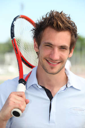 grinning: Male tennis player holding racquet over shoulder