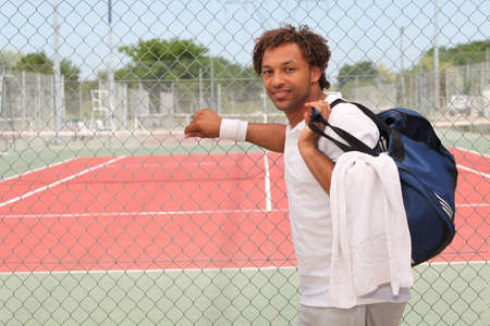 Tennis player with kit bag outside court photo
