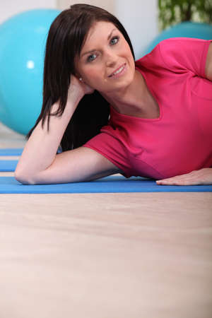 Woman laying on gym mat photo