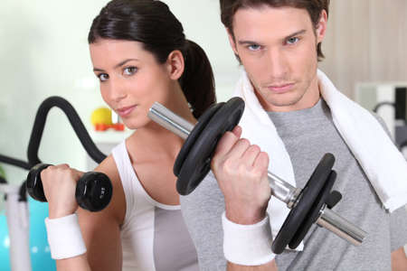 kg: Young woman and young man healthy with barbells Stock Photo