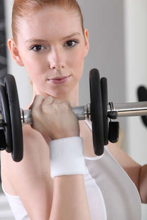 A determined woman lifting a dumbbell photo