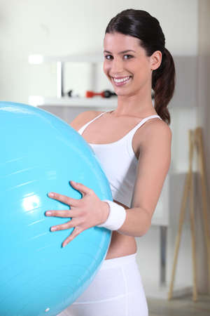 Young woman holding an exercise ball photo