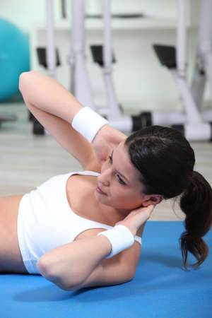 toning: Brunette doing sit-ups in the gym