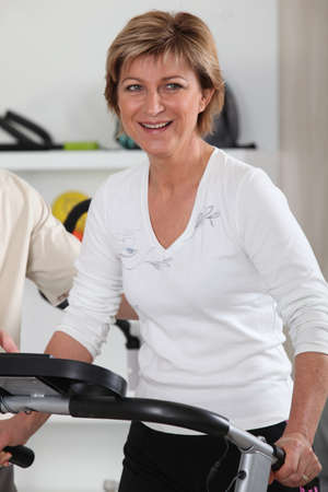 Mature woman using an exercise machine photo
