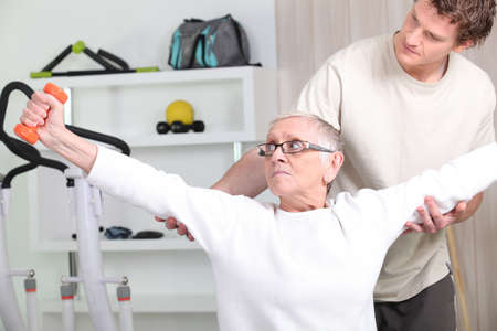 a trainer helping a senior woman doing fitness photo