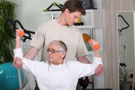 aide à la personne: Senior femme travaillant avec un entraîneur personnel