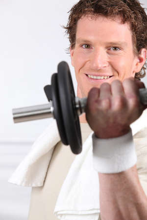 young man doing exercises with a dumbbell photo
