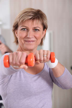 50 55: Woman working out at the gym Stock Photo