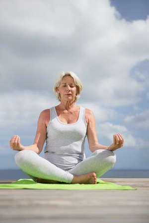mature woman meditating photo