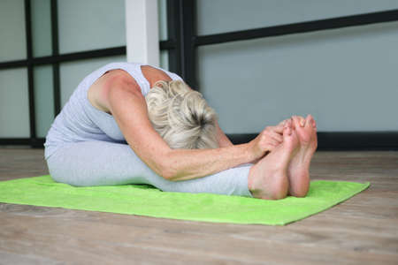touching toes: Mature woman practicing yoga