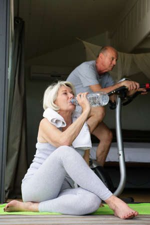 Older couple exercising at home photo