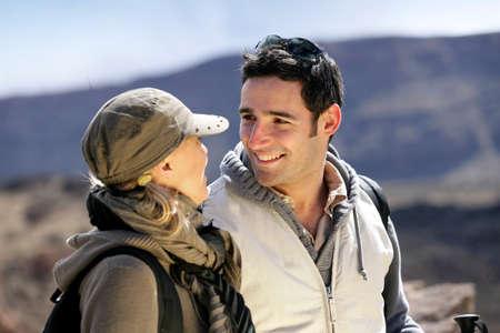 Happy couple hiking through the mountains photo