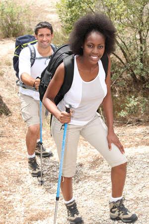 walking pole: mixed couple rambling through nature with walking pole