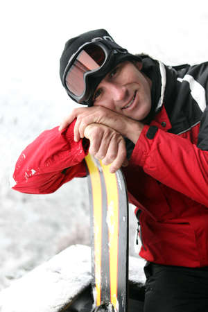 leaning by barrier: Man on a skiing holiday Stock Photo