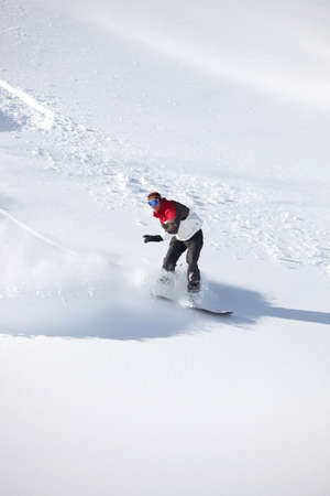 Adventurous man snowboarding down hill photo
