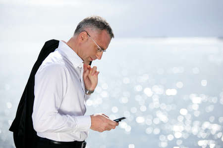 sea side: Businessman sending a text message by the seaside Stock Photo