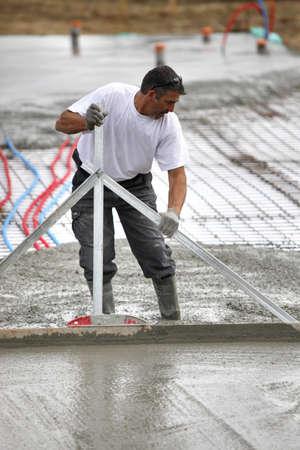 formwork: Man spreading wet cement