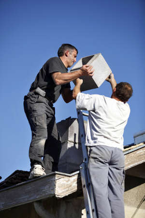 Roofers installing chimney Stock Photo