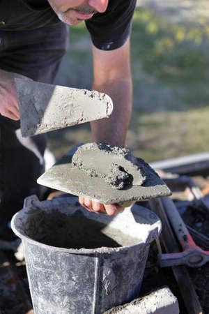 bricklayer: El hombre con el cemento y la paleta Foto de archivo