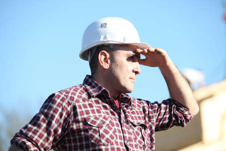 bothered: Tradesman shielding his eyes from the sunlight