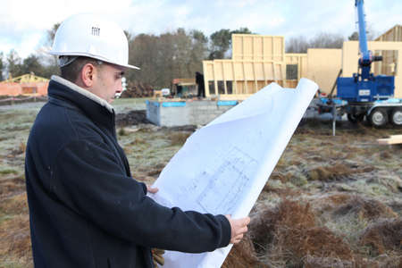 scrutinise: Construction worker examining a blueprint