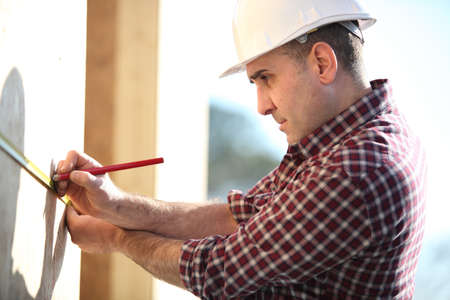 kitchen remodelling: Carpenter marking wooden panel