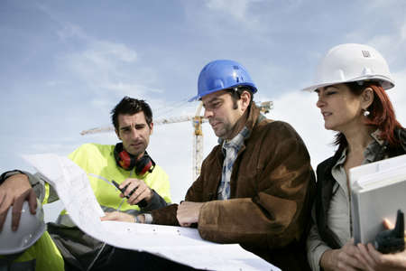 construction helmet: Construction workers discussing plans