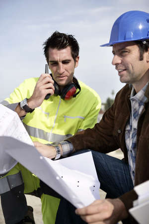 Site engineers with a walky talky Stock Photo - 14212678