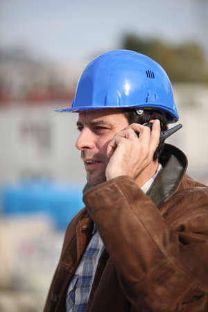 talkie: Construction worker speaking into his walkie-talkie