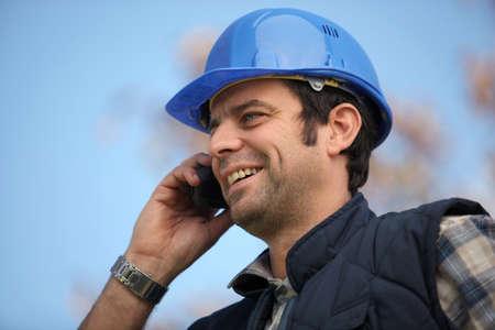 Foreman talking to colleagues via radio photo