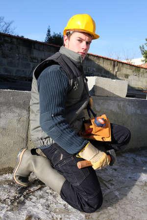 walling: Mason working on building foundations Stock Photo