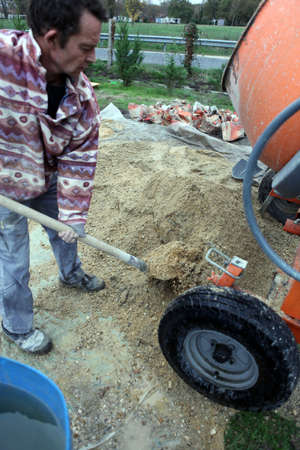 hardworker: Man shovelling gravel into a mixer