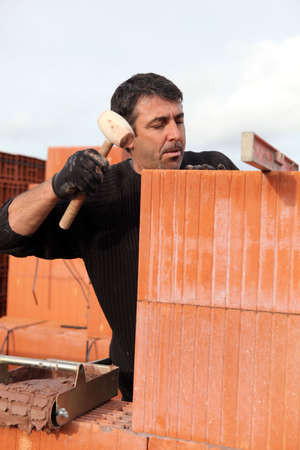 wrongdoing: Man hitting wall with mallet Stock Photo