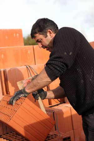 Mason making adjustments to brick photo