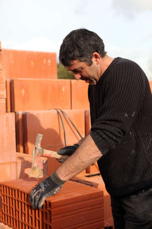 permanence: Builder shaping a brick Stock Photo