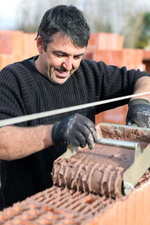 formwork: Mason pouring wet cement on to wall Stock Photo