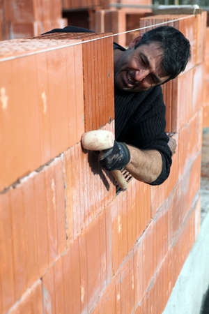 stonemasonry: Man building a brick wall