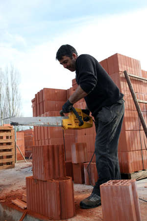 Man sawing through bricks photo