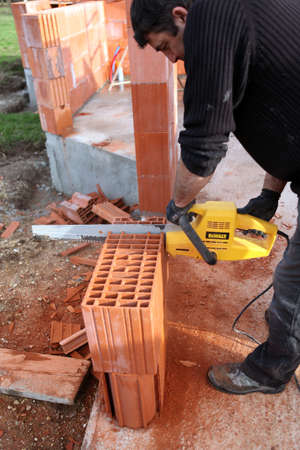 Man using a chainsaw to cut through a brick photo