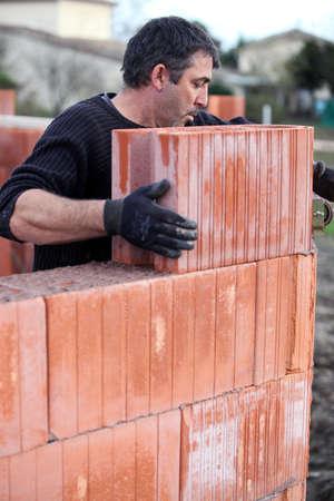 Mason placing brick on unfinished wall photo