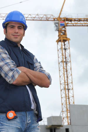construction machinery: Construction worker in front of a crane