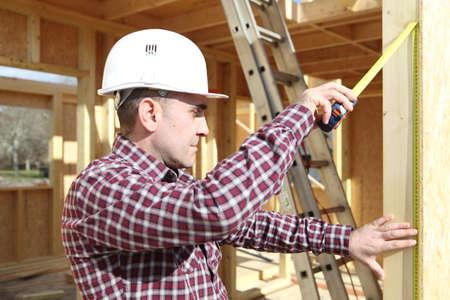 home builder: Carpenter measuring a door frame