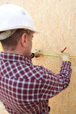 townhome: Man using tape measure to mark wooden panel