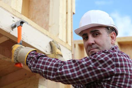 erecting: Man erecting wooden house
