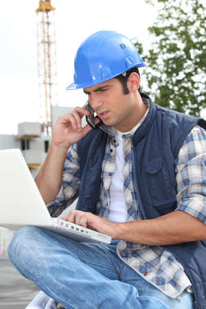 erecting: Construction worker with computer and phone