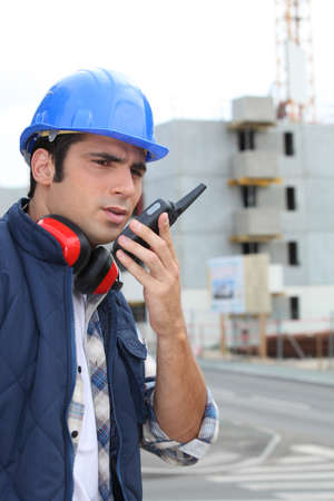 Foreman on construction site giving orders via radio photo
